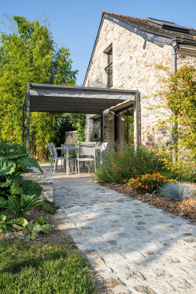 maison en pierre pergola métal jardin
