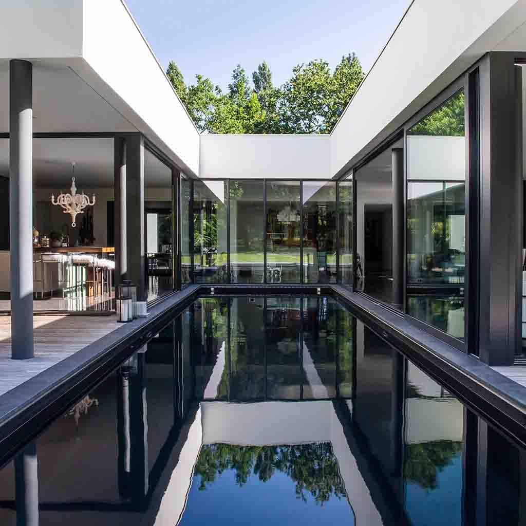 Maison d'architecte en U avec piscine moderne à fond noir