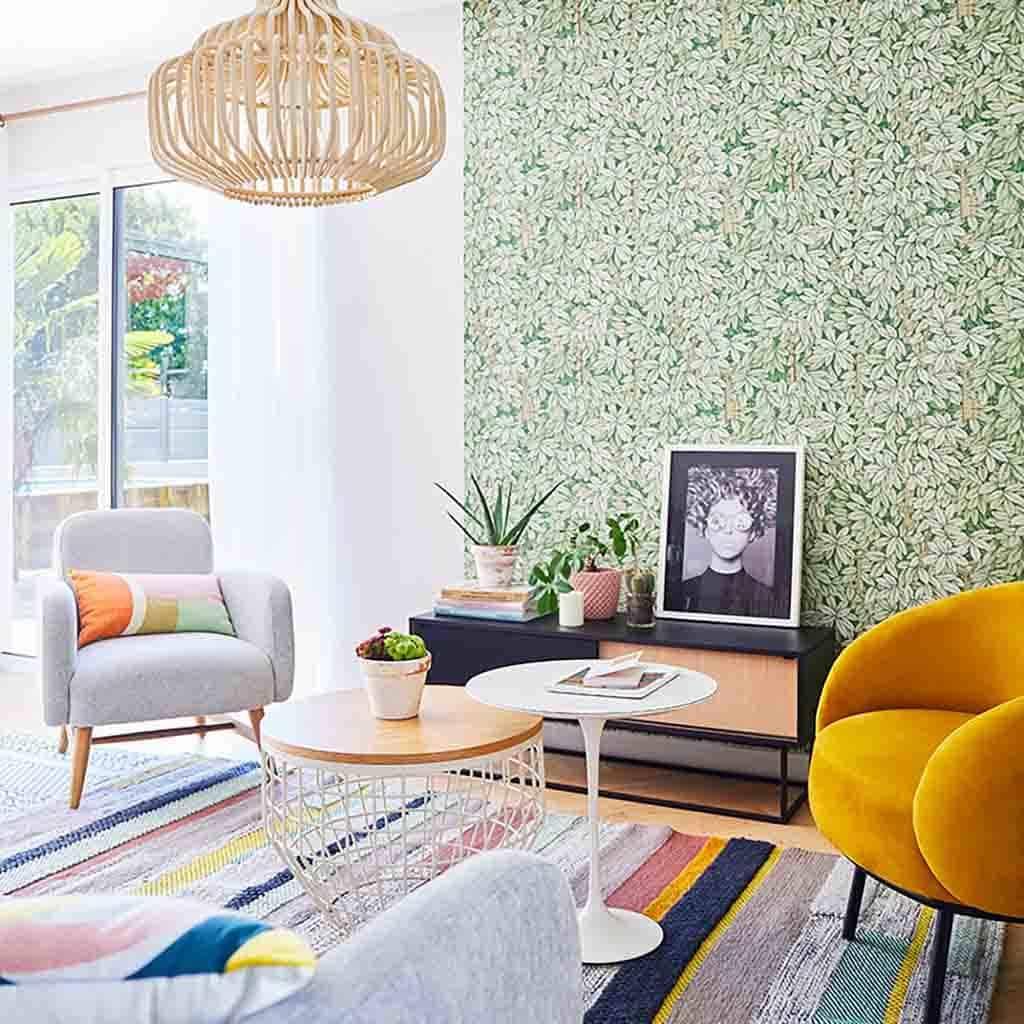 Salon décoré avec des fauteuils en tussus, une suspension en bois et un papier peint feuillage