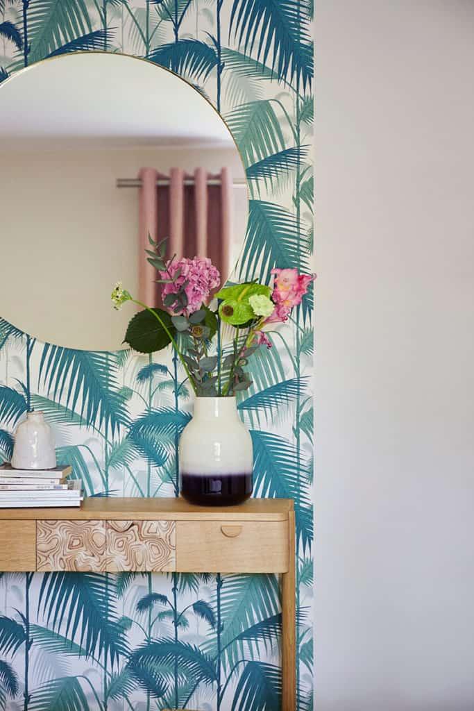 photo de la console en bois sur fond de papier peint feuillage