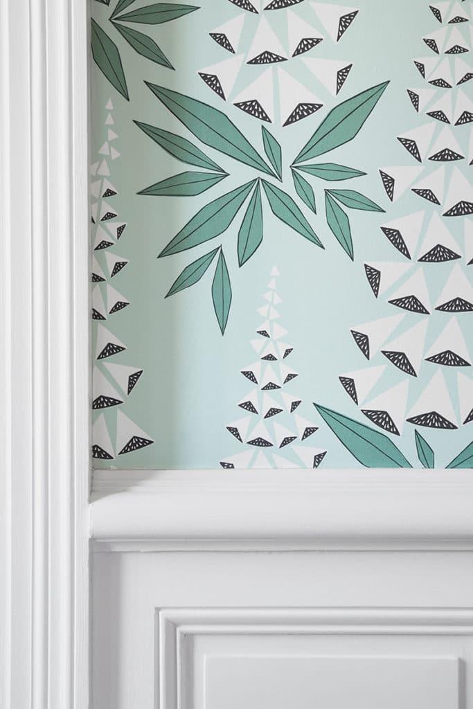 détail de papier peint graphique bleu clair blanc et noir sur murs avec moulures